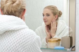 Woman looking in the mirror and touching her face