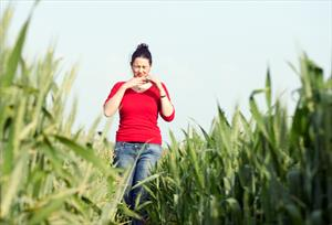 Woman walking in grass looking uncomfortable